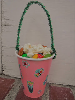 a pink paper cup decorated with flower stickers and a pipe cleaner handle holds popcorn and candy and sits on a brick doorstop in front of a slightly peeling white wood door