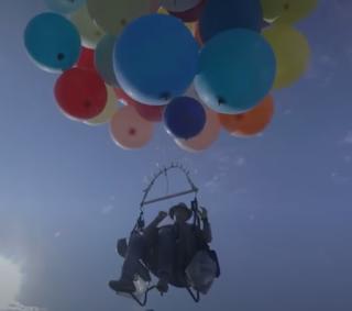 Mann schwebt im Gartenstuhl an Heliumballons.