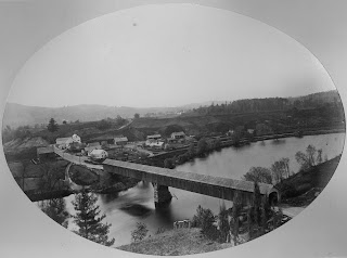 A black and white photograph of a long covered bridge over a river. A small cluster of buildings is on the opposite side.