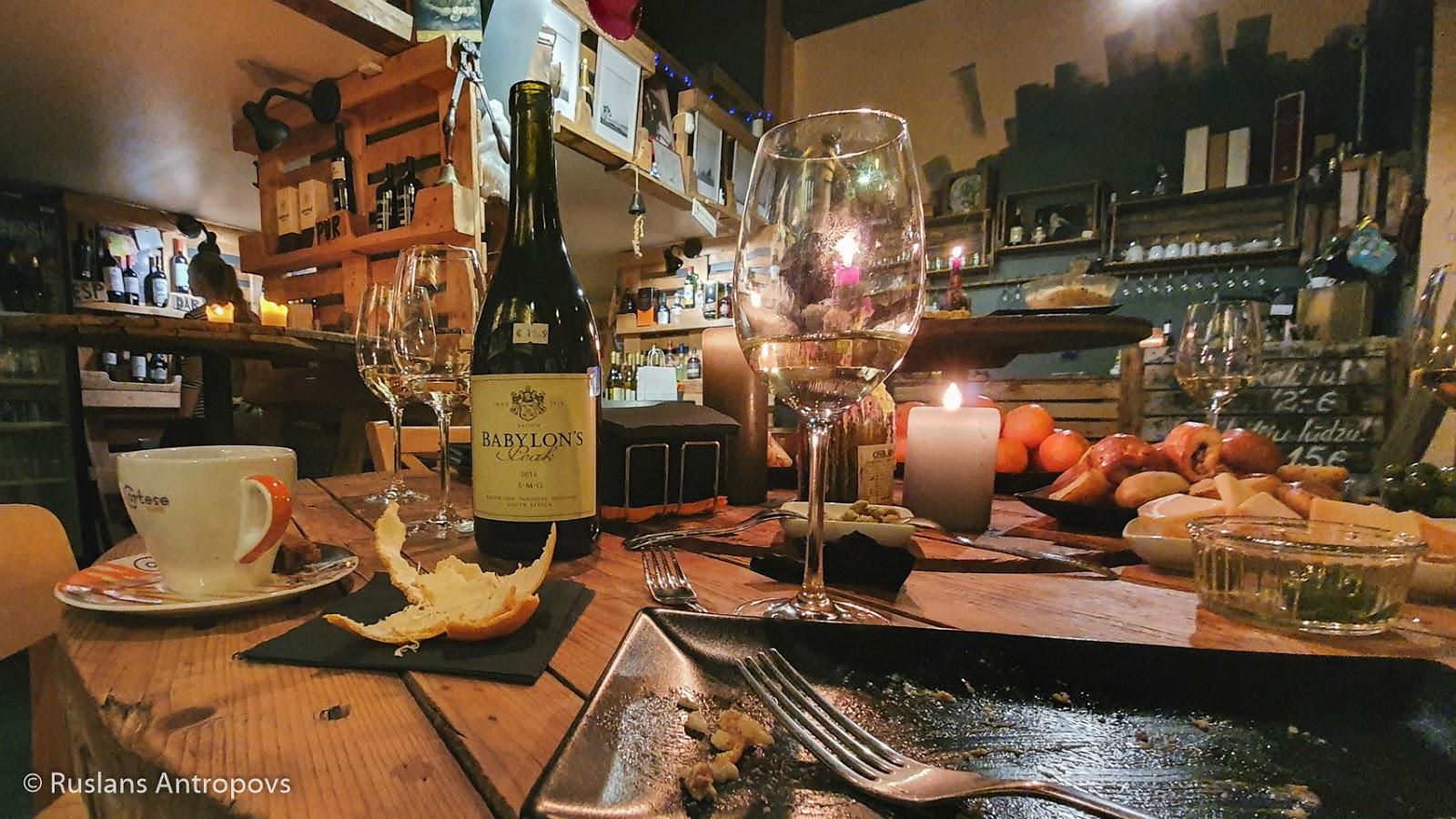 Galds ar vīna glāzēm, vīna pudelēm, kafijas tasītes pēc svētku mielasta