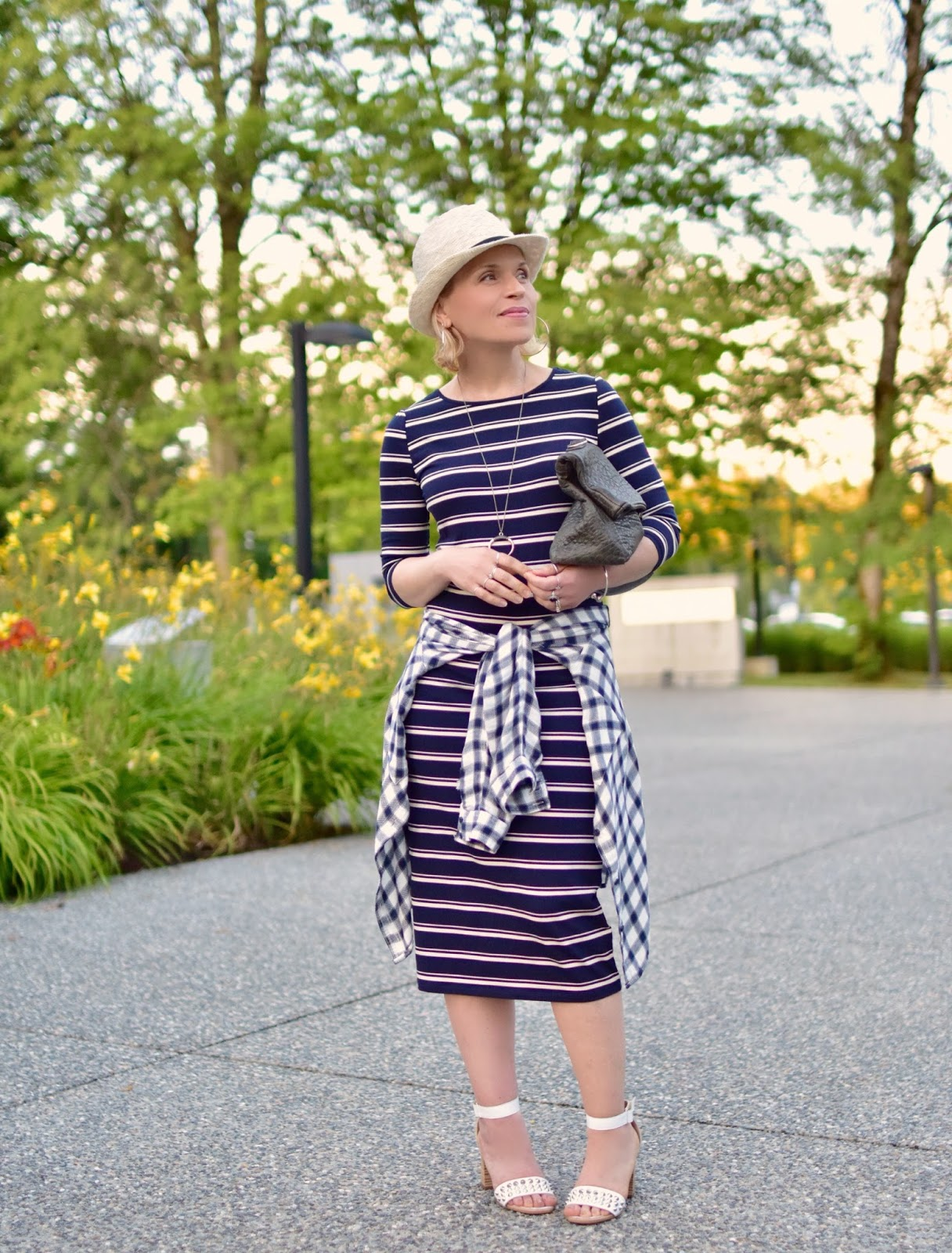 styling a striped t-shirt dress with waist-tied plaid shirt, ankle-strap sandals, and a woven fedora