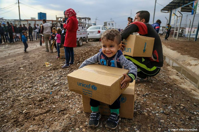 3-year-old Rafi from Syria is all smiles after receiving warm clothing at Kawergosk Refugee Camp in Iraq.
