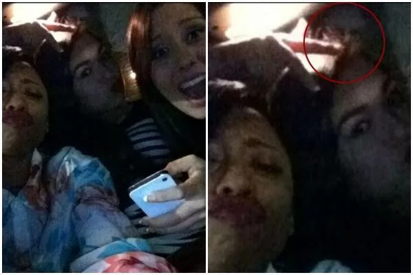The figure of a creepy ghost hitching a ride in the selfie photo of this group of women