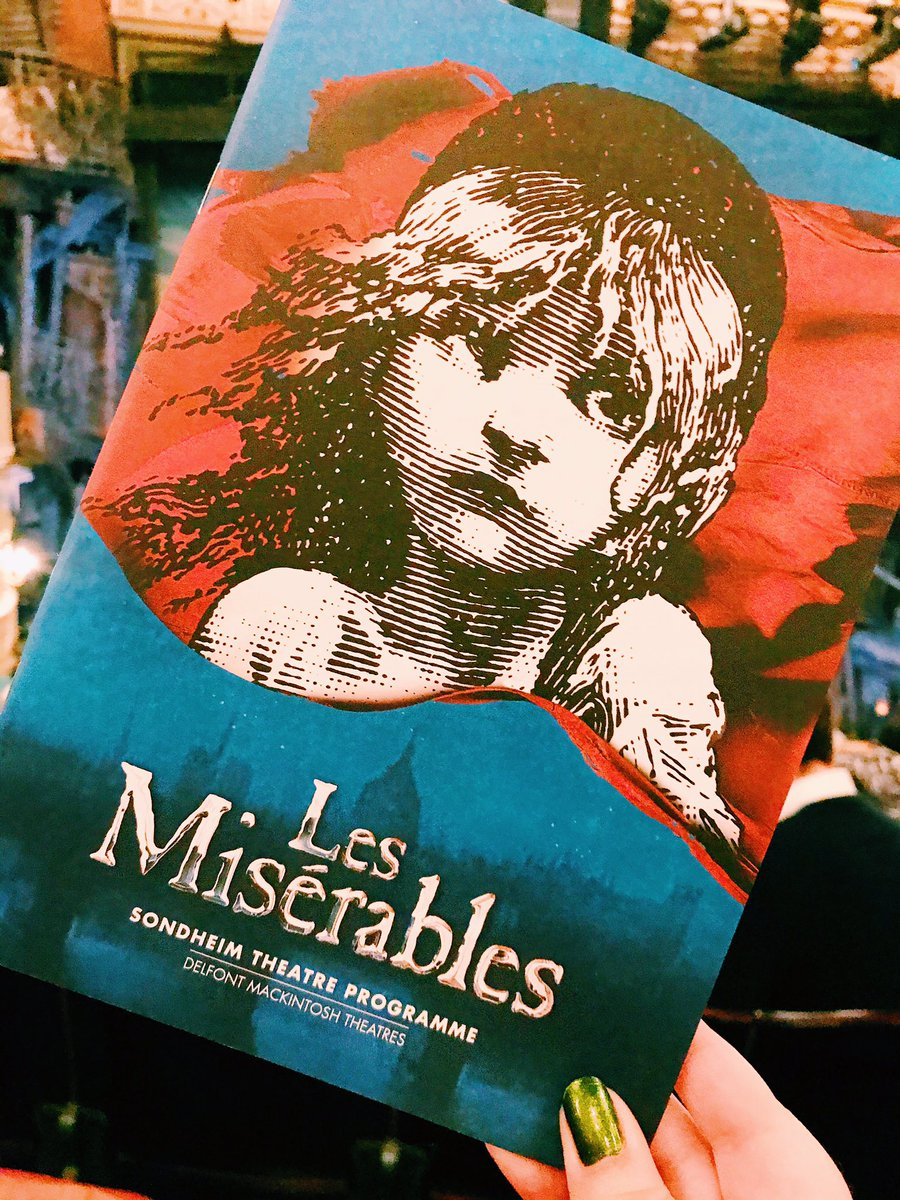 Les Miserables program held up in front of stage
