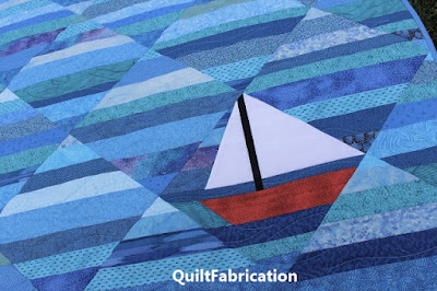 red sailboat in a blue ocean quilt by QuiltFabrication