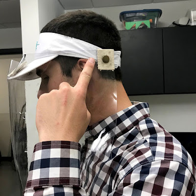 Dan points to a snap on the headband of the face shield