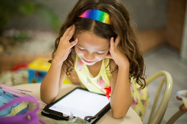 Young girl with a smile, at home staring at a screen