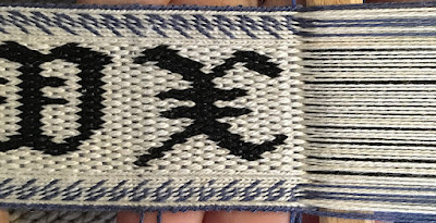 A photo of a section of tablet woven band with the letters W and a new X in black on a white background