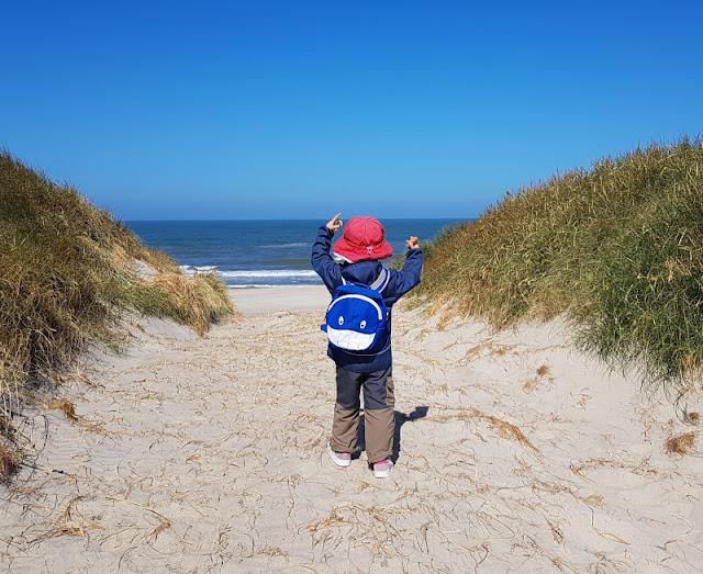 Warum unsere Kinder ihre Rucksäcke selbst tragen (+ Rucksack-Tipps). Beim Ausflug an den Strand in Dänemark trägt unser kleines Mädchen ihren geliebten blauen Hai-Rucksack selber. Sie ist dort ca. drei Jahre alt.