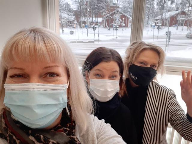 Kolme hymyilevää naista katsoo kameraan maskit naamalla.