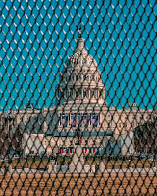 color photograph of US Capitol behind fence after January 6 insurrection