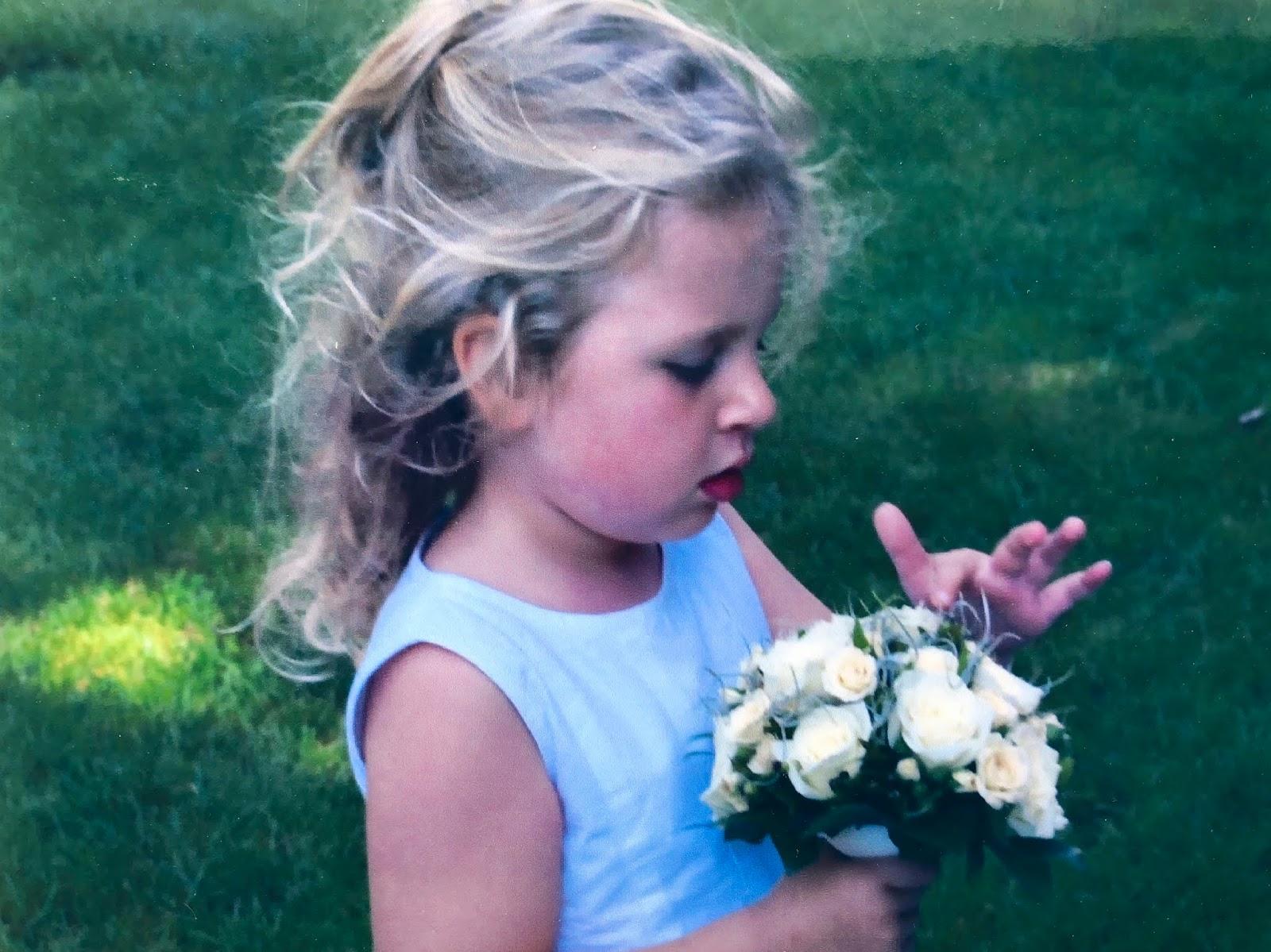 Mijn jongere ik in een wit jurkje en bloemetjes in mijn handen op een grasveld.