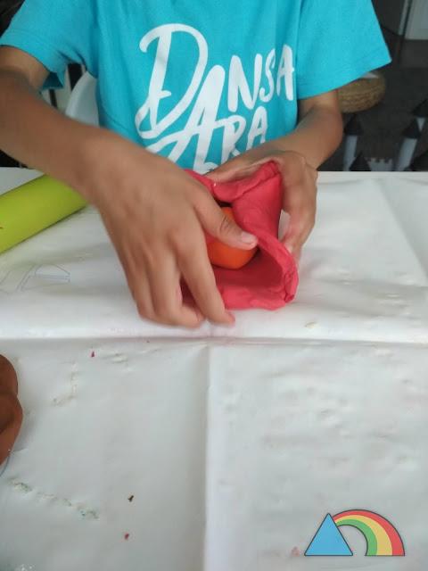 Envolviendo una esfera de plastilina naranja con una capa gruesa de plastilina roja