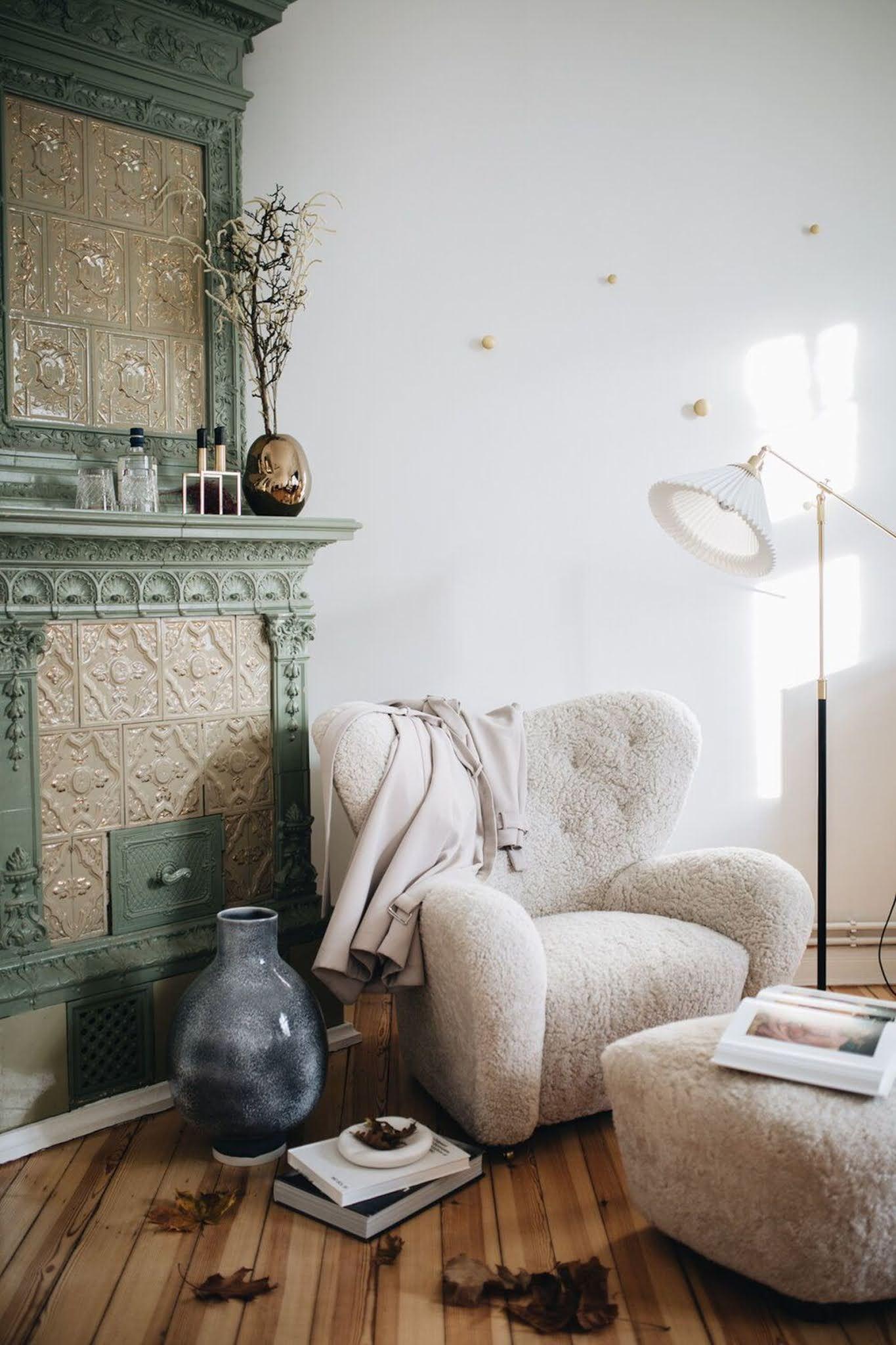 un fauteuil en laine bouclée devant une cheminée sculptée