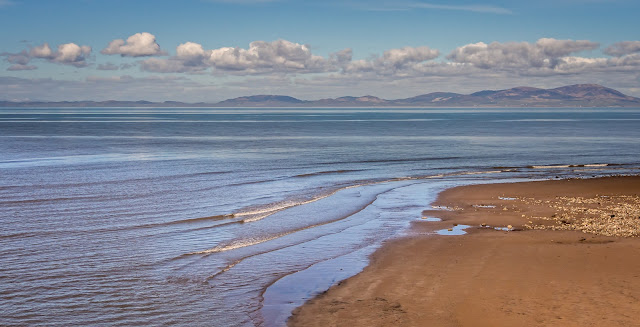 Photo of a calm, sunny day on the beach at Maryport with the Scottish hills in the distance