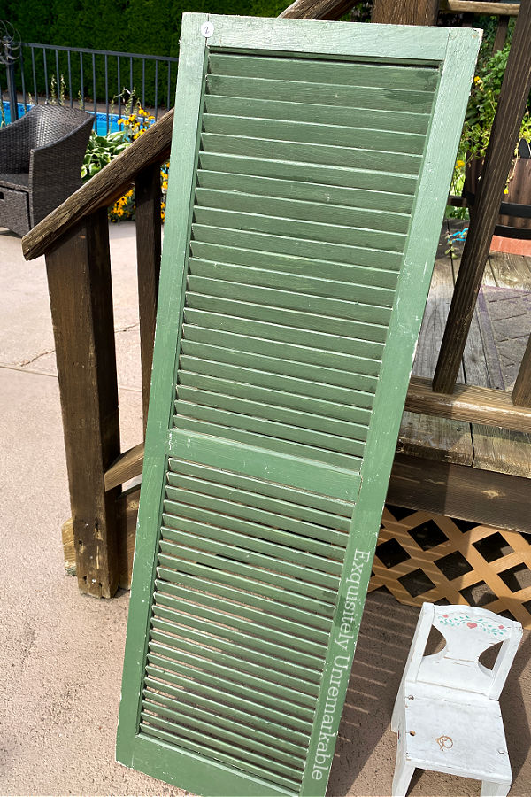 Large Green Painted Shutter propped against a deck