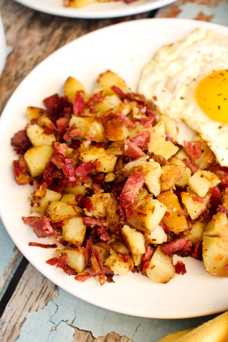 Side view of corned beef hash on a white plate.