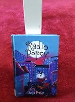 Radio Popov - kirja punaisella matolla nojaamassa valkoiseen pöydänjalkaan