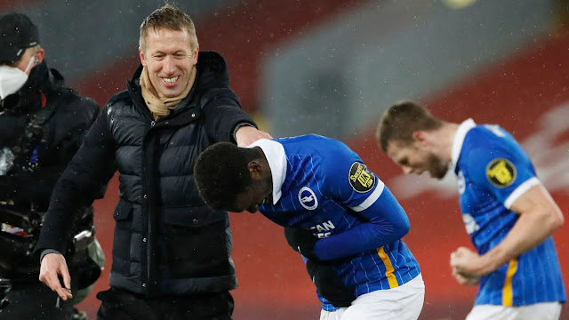 Graham Potter celebrates with his Brighton players as they beat liverpool at anfielda
