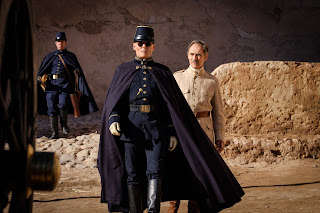 Mark Rylance in beige colonial uniform. Johnny Depp in Navy blue gendarme style uniform with round glasses and cape.