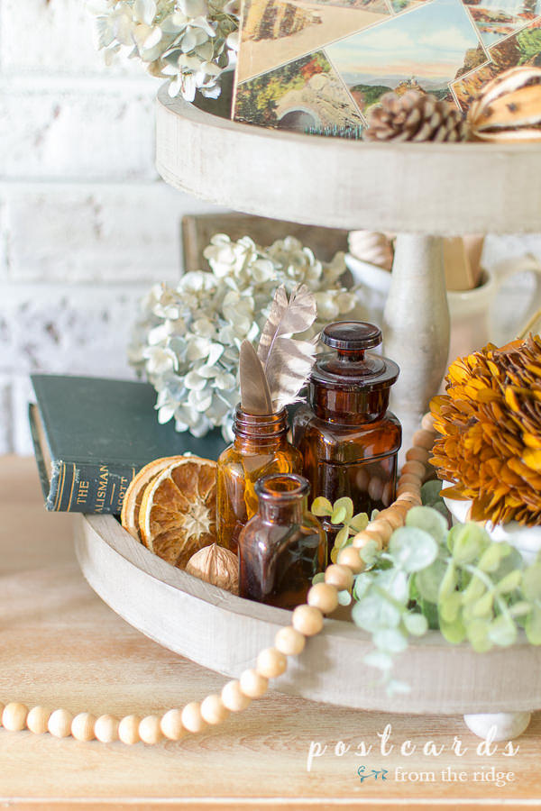 dried oranges, hydrangeas, and amber bottles in a wooden tiered tray