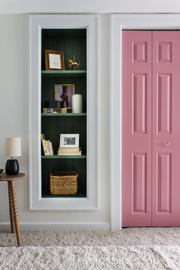 Green built in shelving and pink closet doors