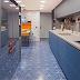 Cozinha azul com ladrilho hidráulico, bancada branca e frontão de inox escovado!