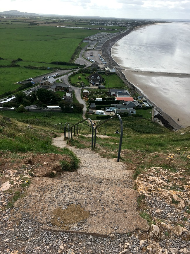 a-walk-on-Brean-Down-steps-looking-down-with-beach-and-carparks-in-the-distance
