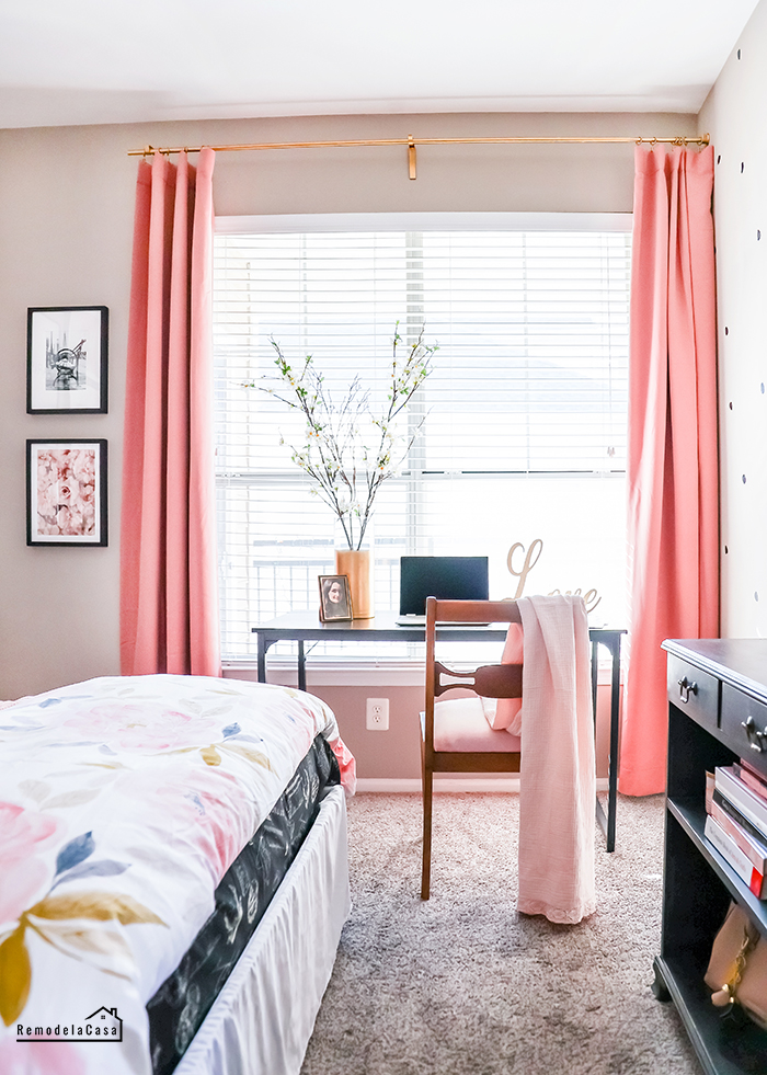 Window with blush pink blackout curtains on gold rod