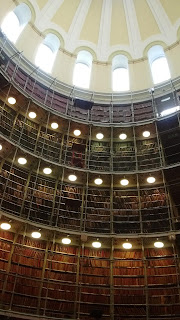 Three floors of bookshelves containing genealogical records, under a domed roof