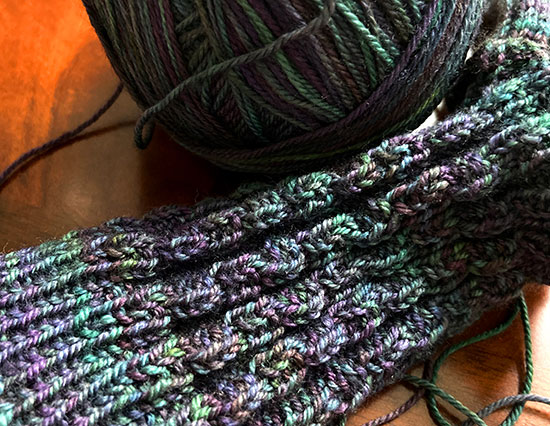 Detail of hand knit chain rib socks in progress with a ball of yarn in the background on a dark wood surface.