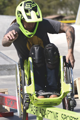 A man in a bright green, manual wheelchair and matching helmet, is shown balancing as he grinds his wheelchair across a railing.