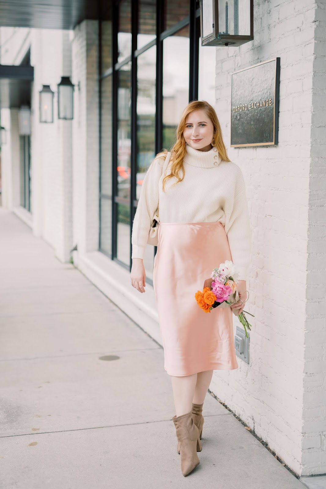 Where to Snag The Best Turtleneck Sweaters Under $50 | Style Blogger Amanda Burrows of Affordable by Amanda wears a cream chunky rib-knit turtleneck from H&M and a pink satin midi skirt from LC Lauren Conrads Kohl's collection at Oxford Exchange in Tampa, Florida. Photo taken by Studio Magnolia.