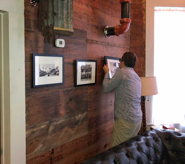 Joe Herring III installing historical images at Pint and Plow