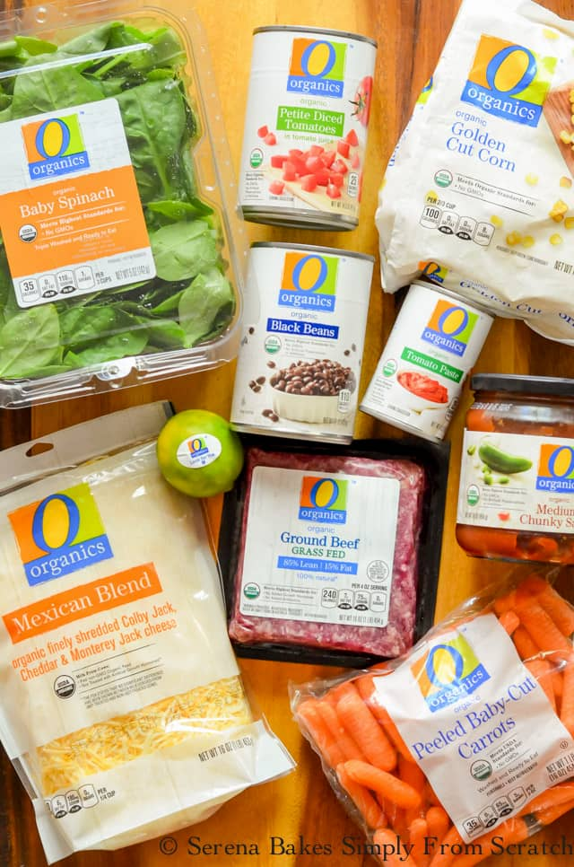 A wooden cutting board with all the O Organics products spread out on the board.