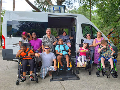 A family is shown in front of their conversion van. A few children are wheelchair users, one of which is positioned on the vehicle's power lift.