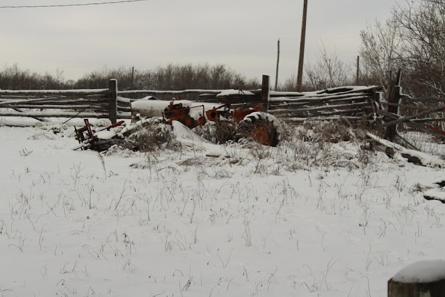 Snow covered rail fence and tractor