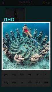 на самом дне водоема находится ансамбль из статуй, а сверху на них смотрит женщина в купальнике