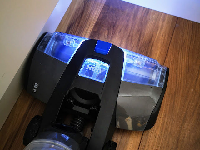 Image of the VAX ONEPWR Hard Floor Cleaner vacuuming close to kitchen cupboards and demonstrating how the LED light helps to identify dirt.