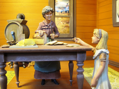 Model of a 19th-century woman and child inside a house. The woman is cutting a loaf of bread, and the child is pointing at a pat of butter.
