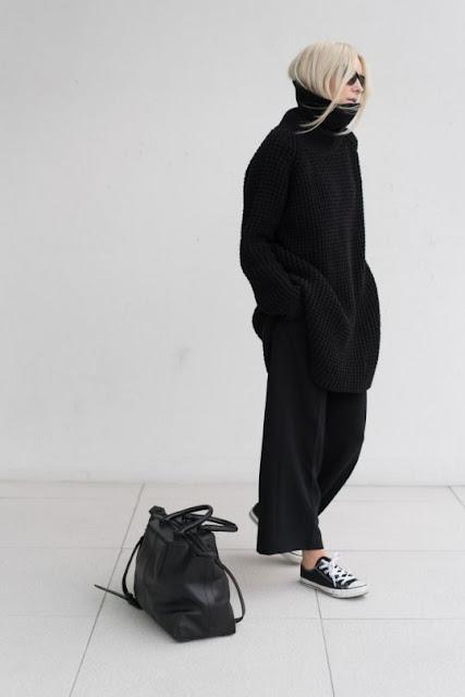 Девушка в черном свитере оверсайз и широких брюках