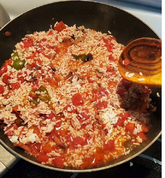 this is a skillet with Spanish rice that has peppers, white rice, diced tomatoes and garlic in it