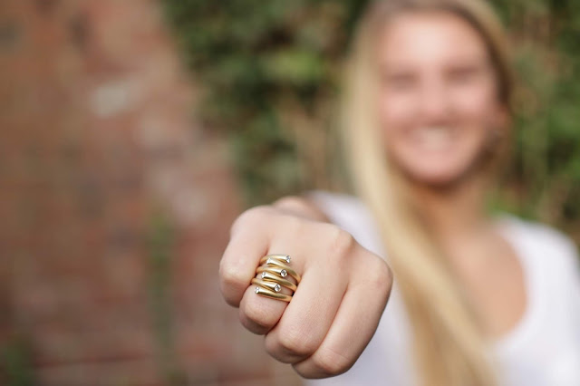 Close up of woman wearing gold statement ring.