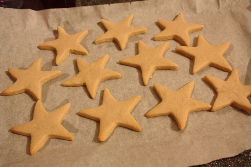 star shaped sugar cookies just out of the oven, on a baking sheet
