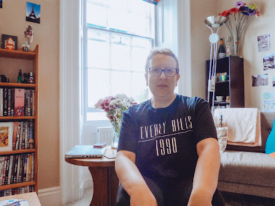 Sarah sat on a stool wearing a black t-shirt that says 'Beverley Hills 1990'