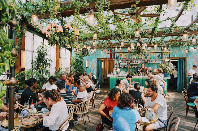 The image shows a pretty canopy with groups of people sitting round tables and enjoying meals. It is an outdoor restaurant with people laughing and sitting on wicker chairs