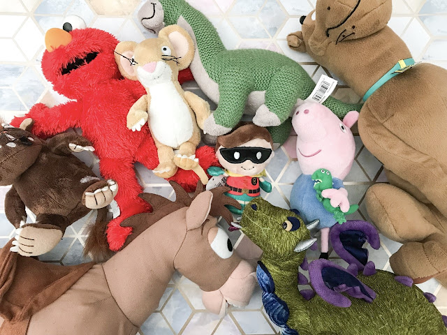 Flatlay showing lots of soft toys needing storage including The Gruffalo, Elmo, Bullseye, Scooby Doo and a dinosaur
