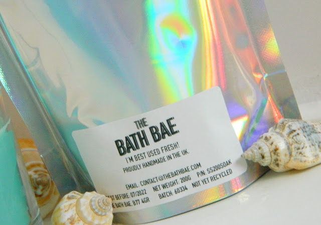 A photo showing a silver iridescent packaging with light reflected in the surface, showing rainbow colours