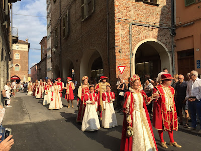 The procession of Borgo San Bernardo dressed in and white as they head to the palio.