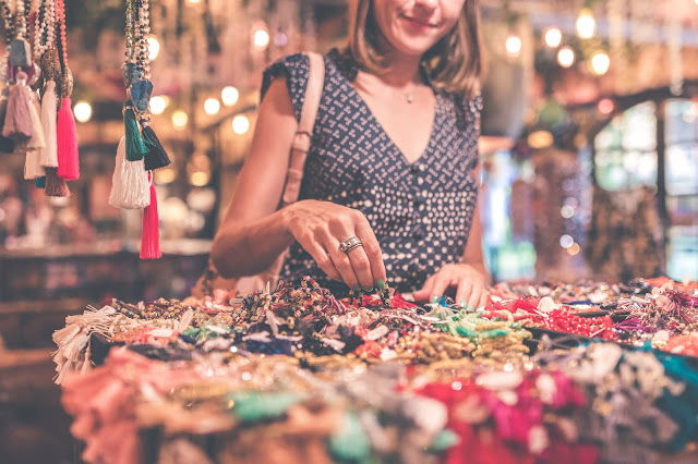 A lady shopping for jewelry at a bazaar.